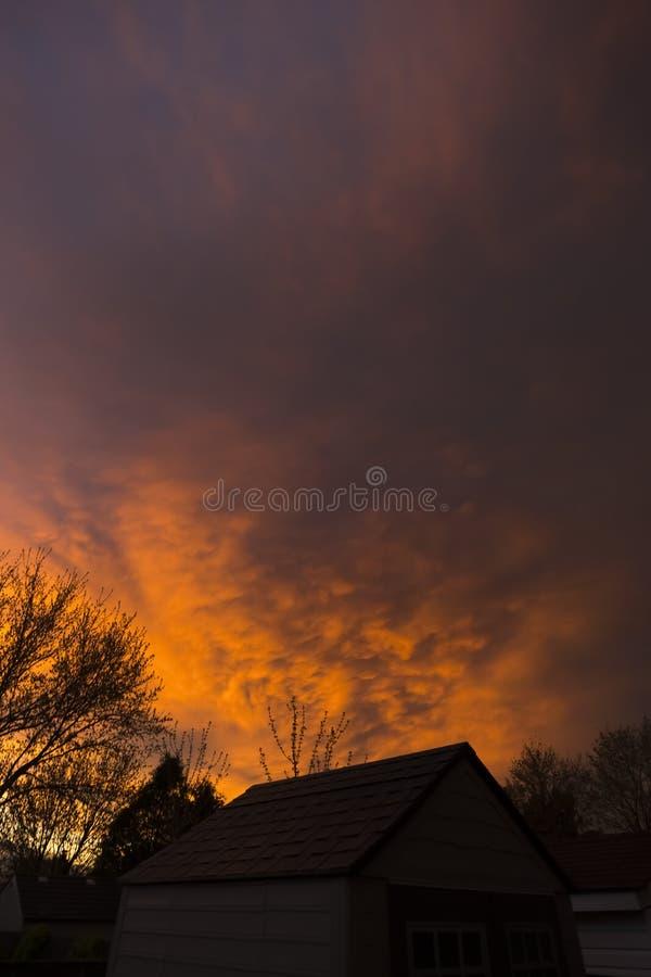 Profundamente ardientemente puesta del sol roja y nubes tempestuosas sobre casas de la vecindad imagenes de archivo