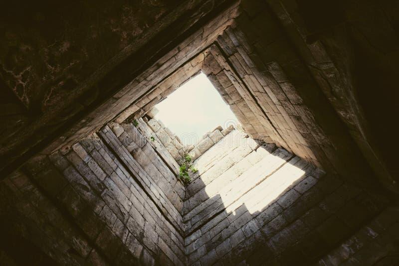 Profundamente pozo, las paredes cuyo se alinean con la piedra Visi?n inferior Luz en el extremo del t?nel Luz en el extremo del c imagen de archivo libre de regalías
