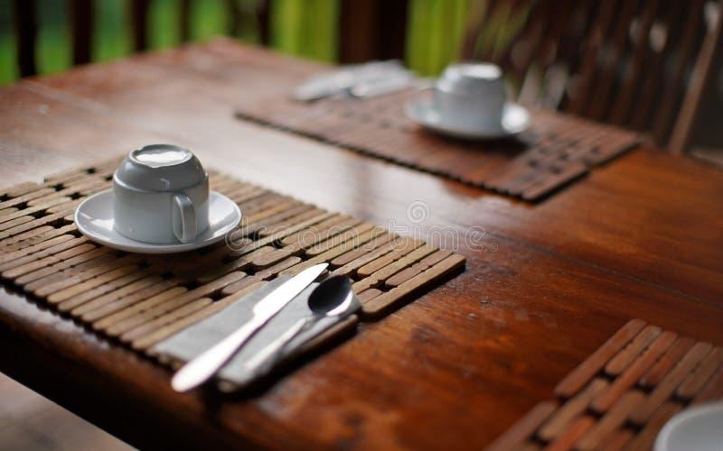Profundidade rasa da foto do detalhe do campo do copo de café vazio de cabeça para baixo na mesa de madeira da tabela, café da ma fotografia de stock royalty free