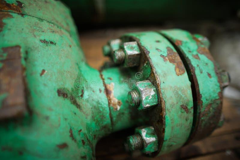 Profundidade rasa da imagem do campo com o equipamento industrial para fora do ferro pesado gasto usado nos parafusos oxidados da fotos de stock