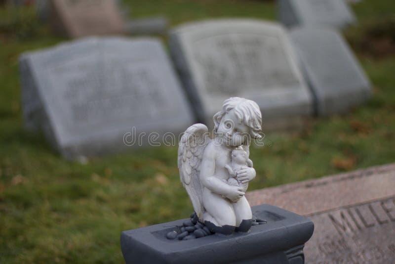 Profundidade rasa do dia exterior da foto do estoque do campo do anjo na lápide no cemitério da esperança da montagem fotos de stock