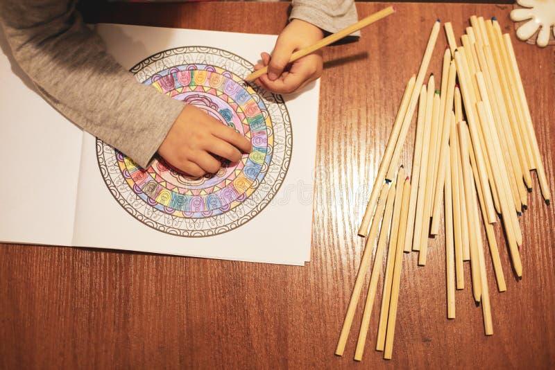 Profundidade suave da imagem de foco seletivo de campo com uma menina colorindo um livro de coloração fotos de stock