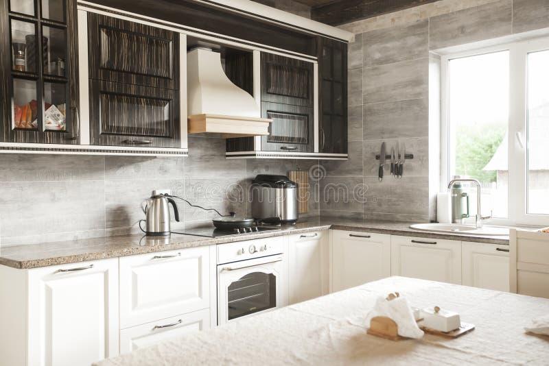 Progettazione compilata leggera della cucina, gabinetti marroni naturali completati con i controsoffitti del granito immagini stock libere da diritti