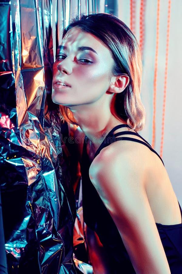 Progettazione d'avanguardia di arte di trucco Bella donna sexy in un fondo al neon rosso brillante, punti culminanti colorati di  immagini stock