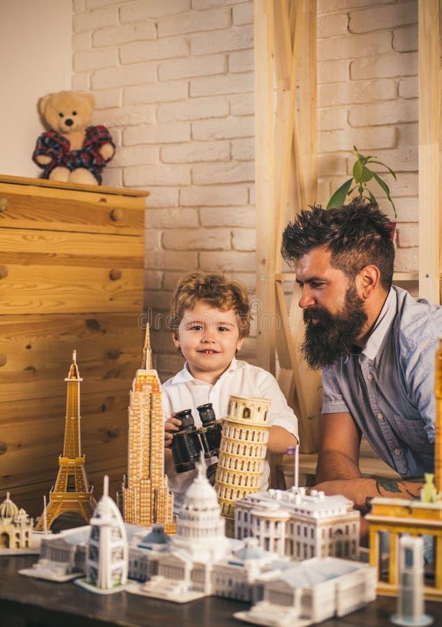 Progettazione del loro viaggio Ricerca dell'avventura Uomo e piccolo bambino con architettura binoculare e miniatura Figlio del r fotografie stock