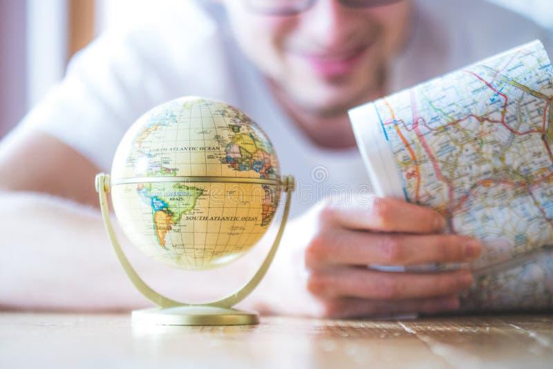 Progettazione del viaggio seguente: Uomo con la mappa e globo miniatura sul pavimento fotografia stock