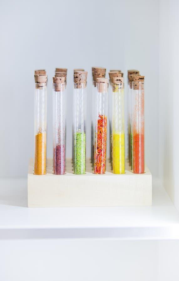 Progettazione della cucina, serbatoi per la spezia sotto forma di provette chimiche Varie spezie colorate nella cucina: paprica,  fotografia stock libera da diritti
