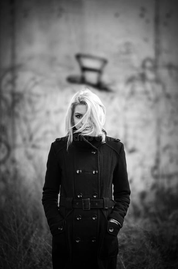 Progettazione di orrore di concetto con la ragazza in cappotto nero immagine stock libera da diritti