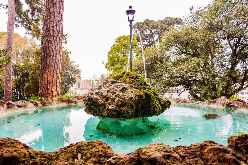 Progettazione di pietra rocciosa della fontana con chiara acqua trasparente blu che riflette il cielo ed il getto di scorrimenti  immagine stock