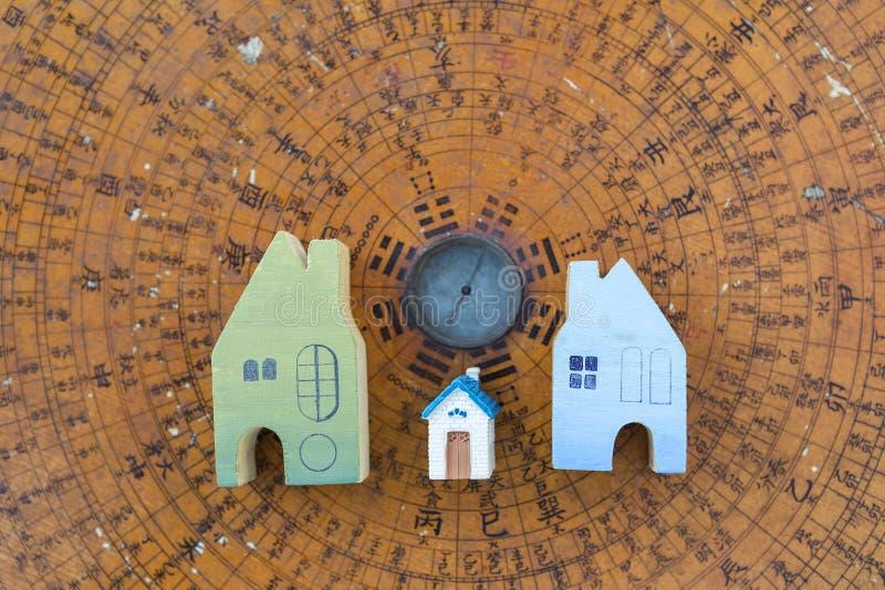 Progettazione miniatura della casa sul fondo di legno antico della bussola di feng shui fotografia stock libera da diritti