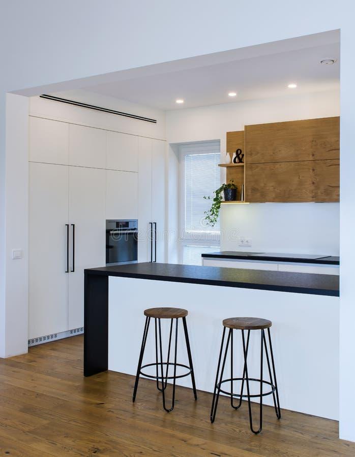 Progettazione moderna della cucina nell'interno leggero con gli accenti di legno immagini stock