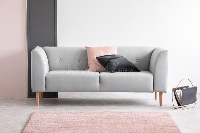 Progettazione rosa e nera pastello in salone elegante interno con il sofà comodo, foto reale con lo spazio della copia fotografia stock libera da diritti