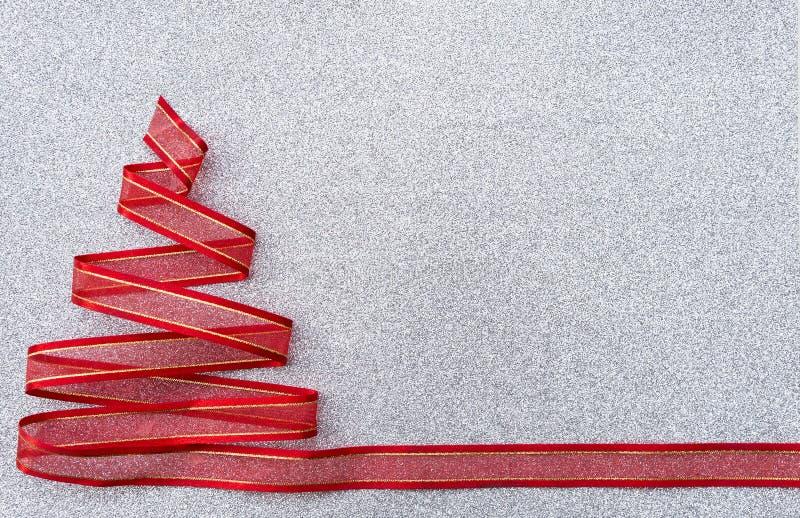 Progettazione rossa dell'albero di Natale del nastro sul fondo d'argento di struttura di scintillio fotografia stock