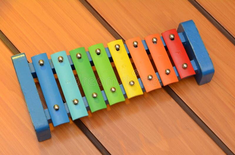 Progettazione variopinta dello xilofono dei campanelli su fondo di legno immagini stock