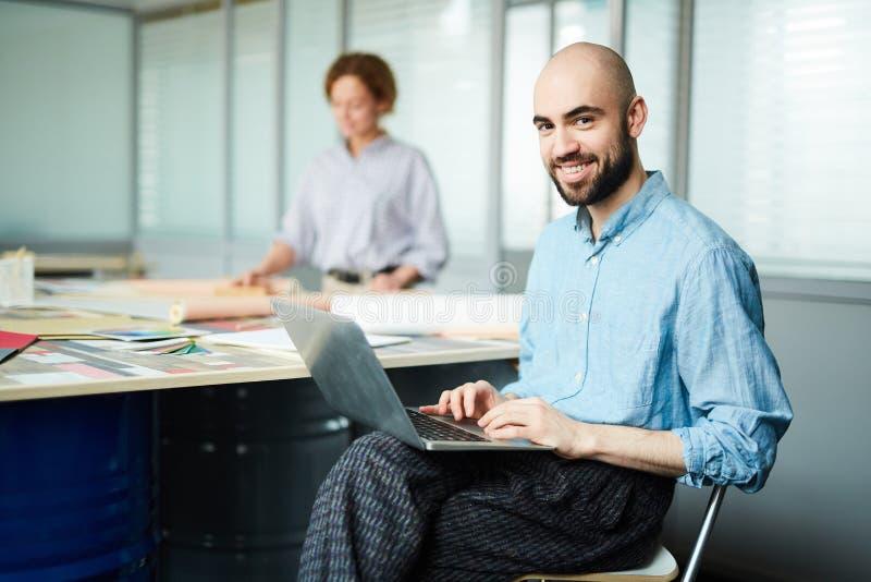 Progettista allegro di web che utilizza computer portatile nell'ufficio dello spazio aperto fotografia stock libera da diritti
