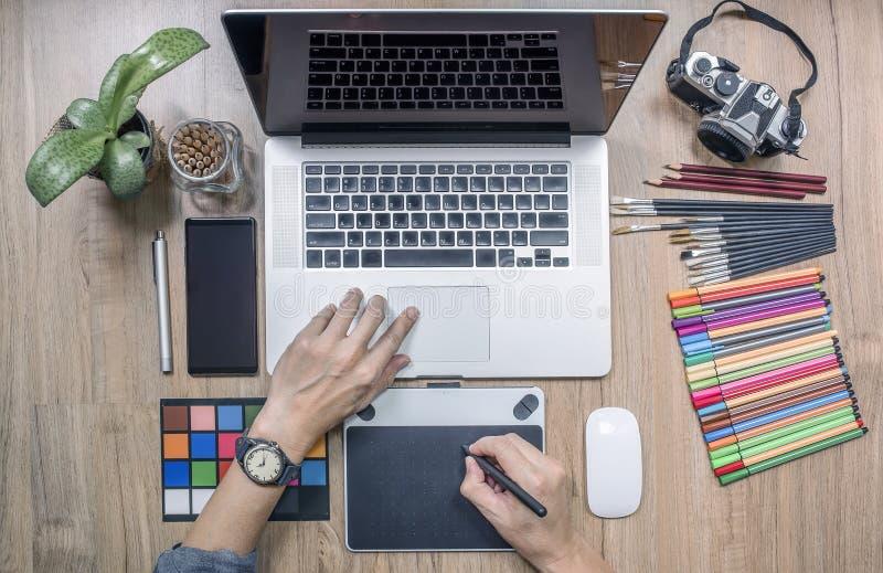 Progettista che per mezzo del computer portatile e della tavola dei grafici a casa offic fotografie stock libere da diritti