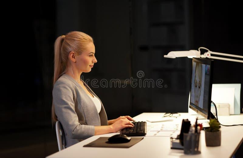 Progettista con il computer che funziona vicino all'ufficio fotografie stock