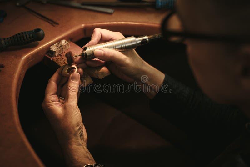 Progettista dei gioielli che lucida un anello fotografie stock libere da diritti