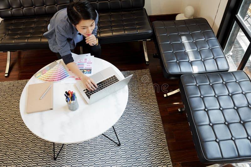 Progettista della donna che lavora online sul computer portatile fotografie stock libere da diritti