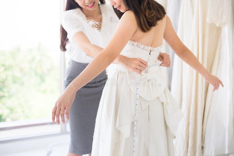 Progettista felice della donna che procede all'adeguamento nello studio di modo, sposa asiatica che smling e che prova sul vestit fotografie stock