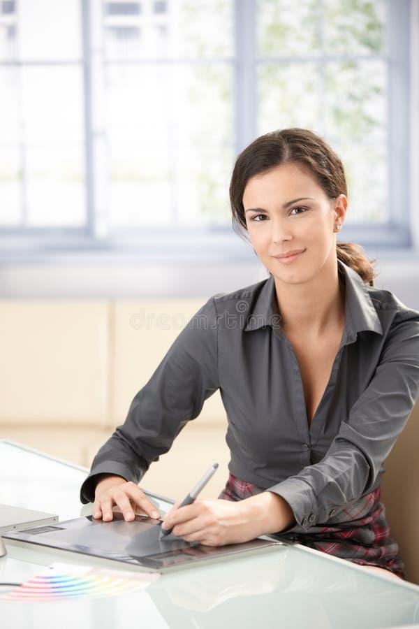 Progettista grafico femminile che per mezzo del ridurre in pani immagine stock libera da diritti