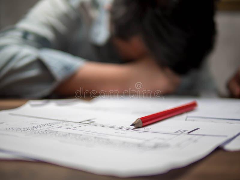 Progettista maschio stanco dei giovani che lavora duro sonno sulla tavola fotografie stock