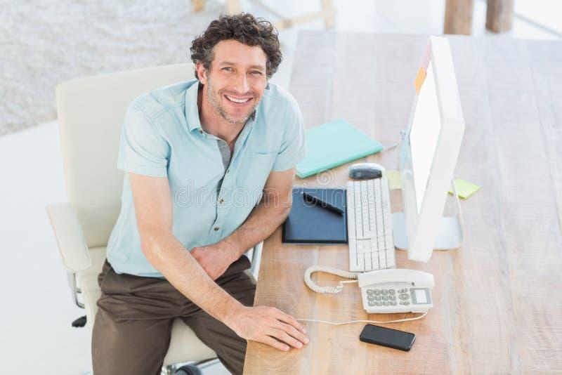 Progettista sorridente che lavora al suo computer immagini stock