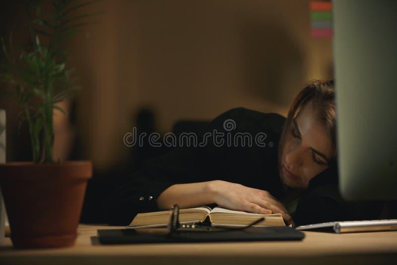 Progettista stanco della giovane signora che dorme all'interno alla notte sul libro fotografia stock libera da diritti
