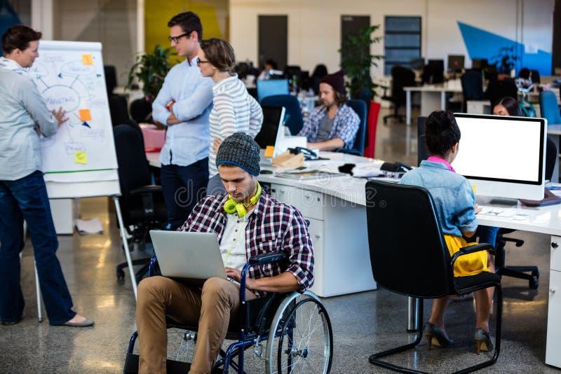 Progettista in una sedia a rotelle con un computer immagine stock libera da diritti