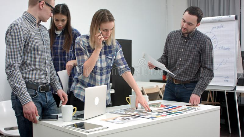 Progettisti che parlano sul telefono con il cliente mentre selezionando i colori a partire dalla tavolozza immagini stock