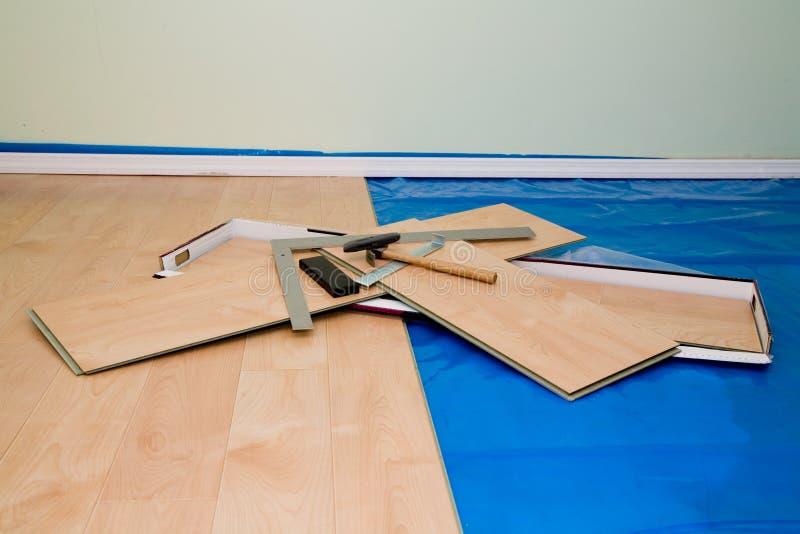 Progetto di DIY: installando pavimento laminato rifinito acero nel vivere immagini stock libere da diritti