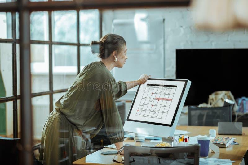 Programação de funcionamento de trabalho da mulher de negócios grávida foto de stock