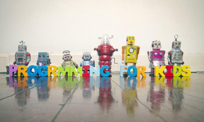 PROGRAMACIÓN PARA LOS NIÑOS con las letras de madera y los robots retros en un w fotos de archivo libres de regalías