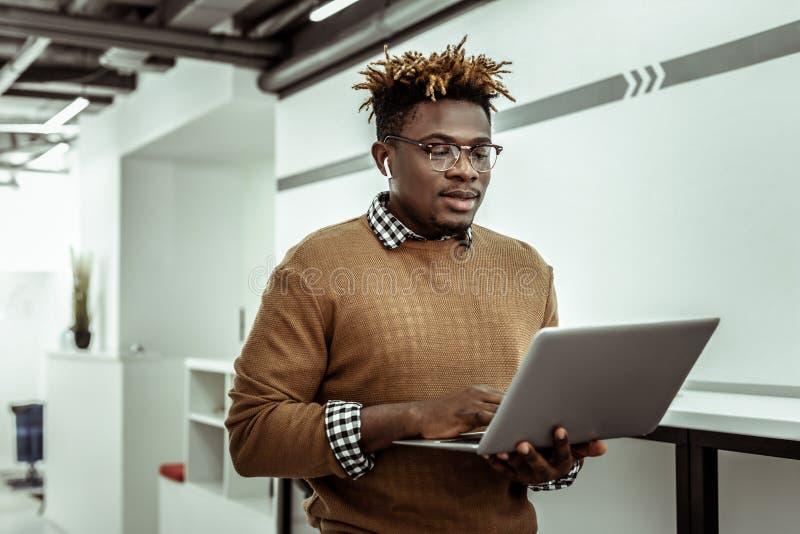 Programador afroamericano en los vidrios claros que sostienen el ordenador portátil foto de archivo libre de regalías
