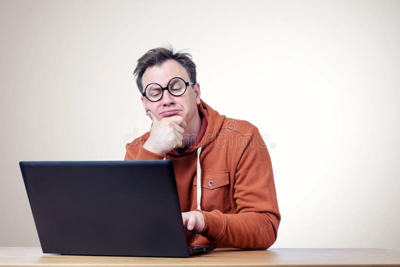 Programador con los vidrios y una camiseta que piensan delante del ordenador portátil fotografía de archivo libre de regalías