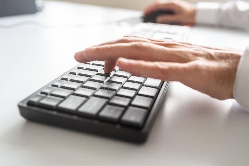 Programador de negócio que usa o teclado e o rato de computador fotos de stock