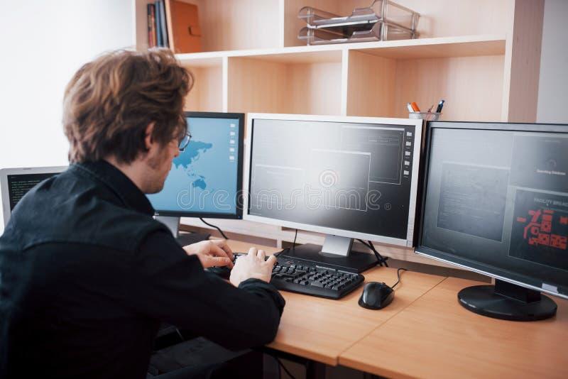 Programador de sexo masculino que trabaja en el equipo de escritorio con muchos monitores en la oficina en software para desarrol imagenes de archivo