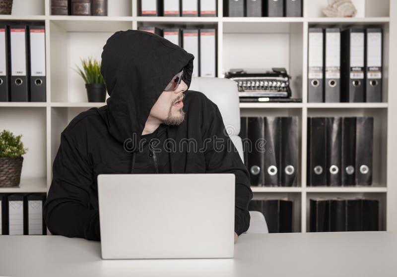 Programador del pirata informático que usa el ordenador portátil en oficina fotografía de archivo libre de regalías