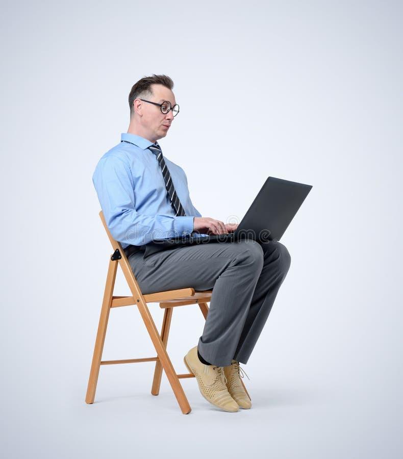Programador divertido con un ordenador portátil que se sienta en una silla en fondo imagenes de archivo