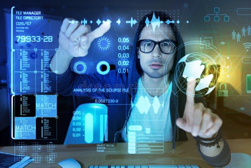 Programador esperto que toca em dois esquemas virtuais e que olha sério fotografia de stock royalty free