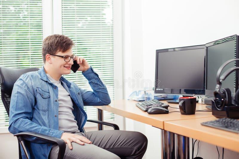 Programador joven que habla en el teléfono móvil fotografía de archivo