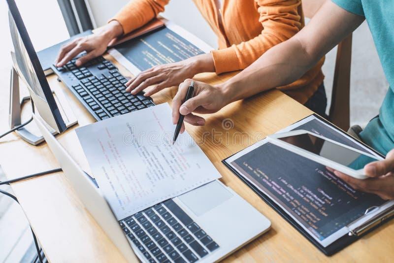 Programador profesional dos que coopera y que trabaja en proyecto de sitio web en un software que se convierte en el equipo de es fotos de archivo