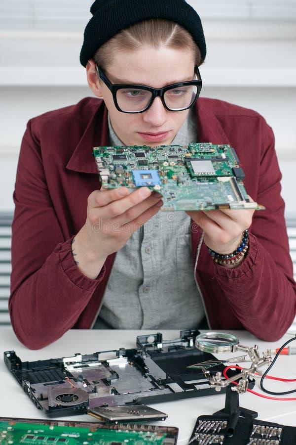 Programador que estuda o processador central quebrado na oficina imagem de stock royalty free