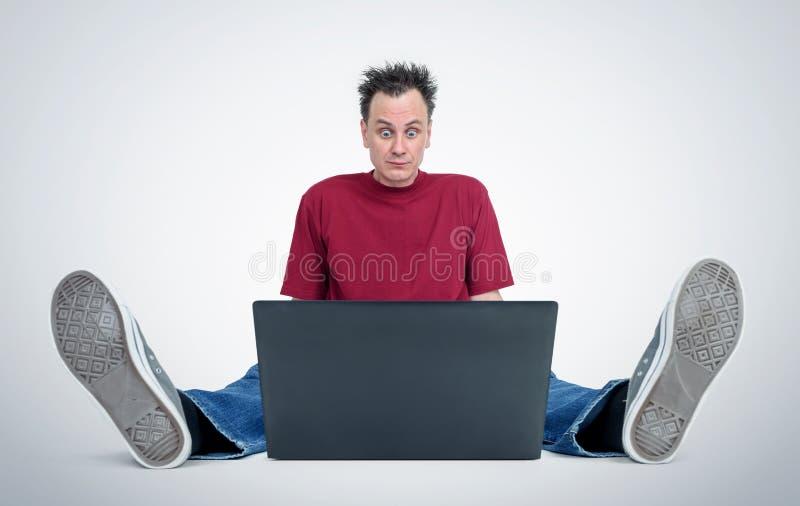 Programador que se sienta en el piso delante de un ordenador portátil imágenes de archivo libres de regalías