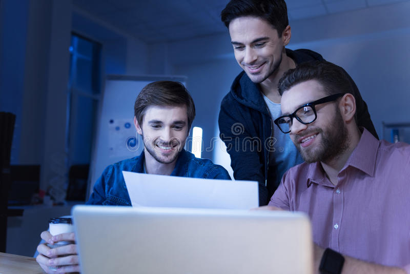 Programadores alegres positivos que apreciam o trabalho junto fotos de stock royalty free