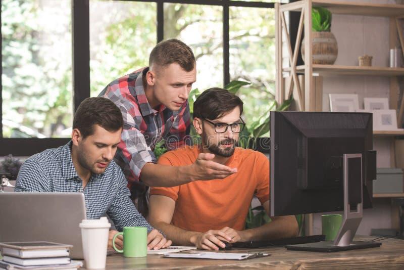 Programadores de los hombres jovenes que trabajan junto en la oficina imagen de archivo libre de regalías
