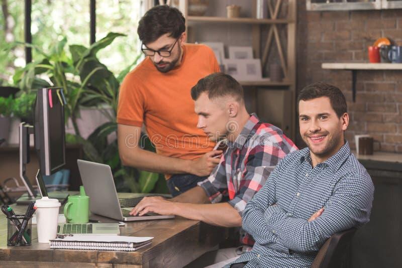 Programadores de los hombres jovenes que trabajan junto en la oficina imagen de archivo