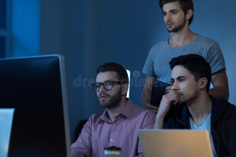 Programadores pensativos consideráveis que olham o tela de computador foto de stock