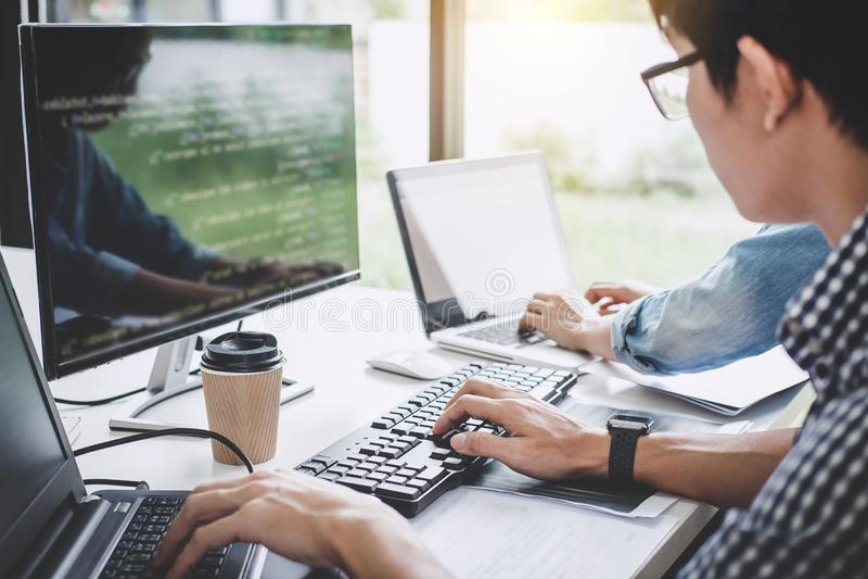 Programadores que cooperan en la programación y el sitio web que se convierten wo foto de archivo