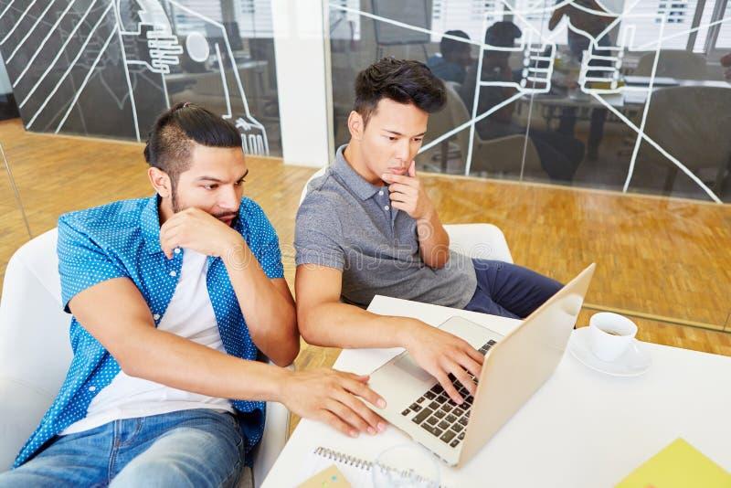 Programadores que trabajan en equipo con el ordenador portátil imagen de archivo